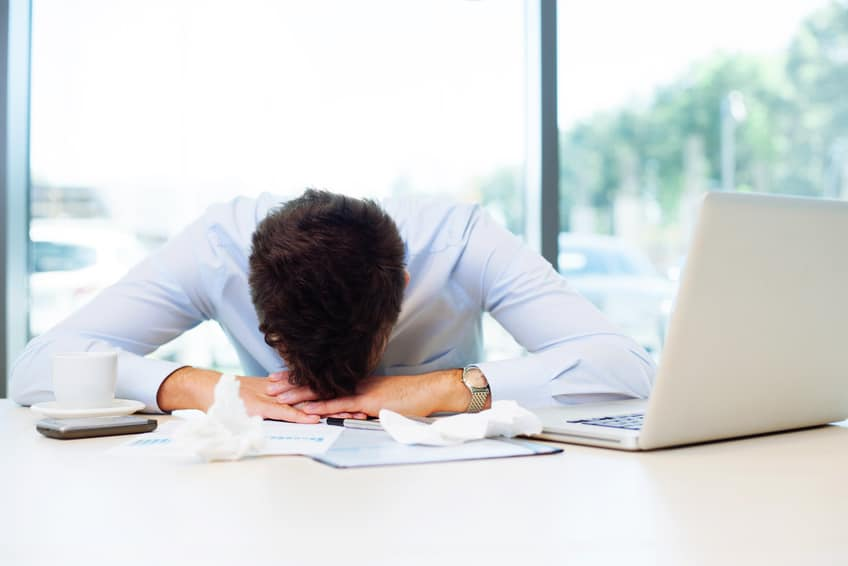 Sick man sleeping at work in the office